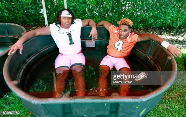 UM's DJ Johnson and Jeff Thomas cool off in a tub of ice water after the second day of University of Miami football camp at Greentree Field on...