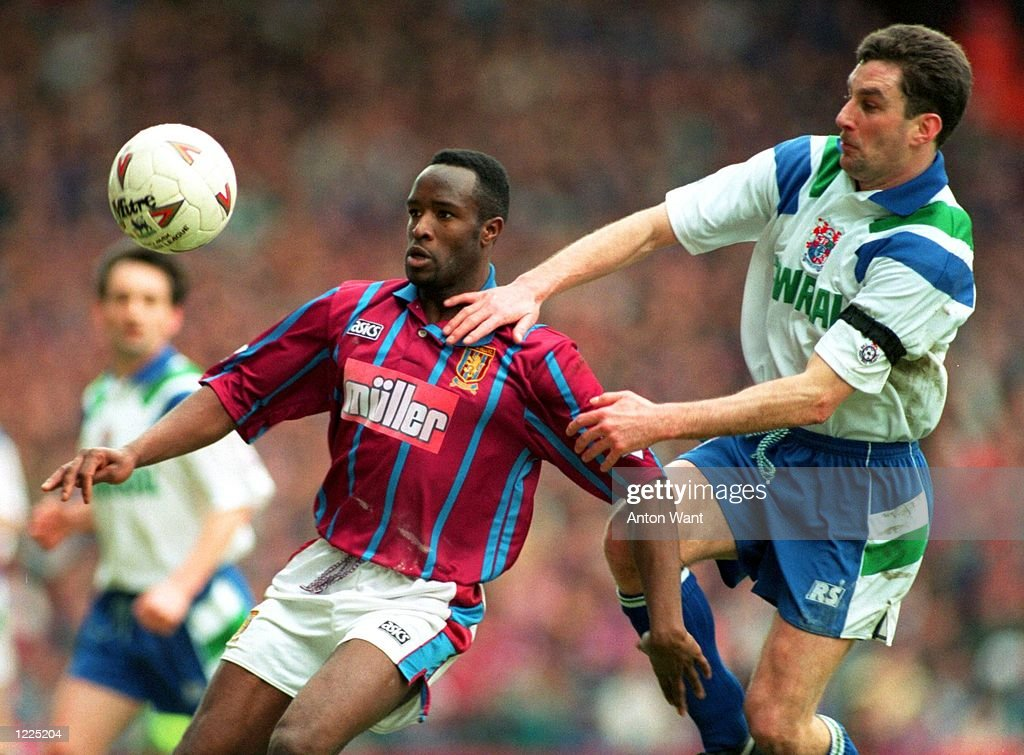 VILLA's EARL BARRETT EYES THE BALL BUT IS HELD BACK BY TRANMERE ROVERS'' JOHN ALDRIDGE IN THEIR COCA-COLA CUP SELIFINAL MATCH TODAY. VILLA WON THE MATCH, 3-1. Mandatory Credit: Anton Want/ALLSPORT