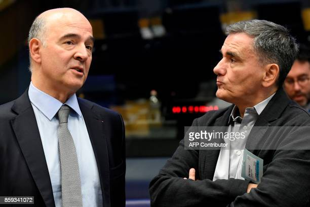 EU's Economic Affairs Commissioner Pierre Moscovici talks with Greece's Finance minister Euclid Tsakalotos during a Eurozone Finance ministers...