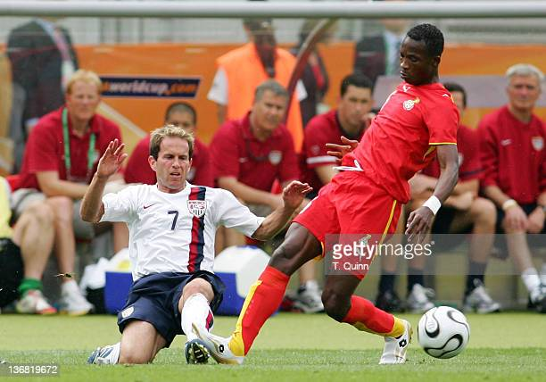 USA's Eddie Lewis slips the ball past Ghana's John Mensah during the Group E game between the USA and Ghana at FrankenStadion in Nuremberg Germany on...