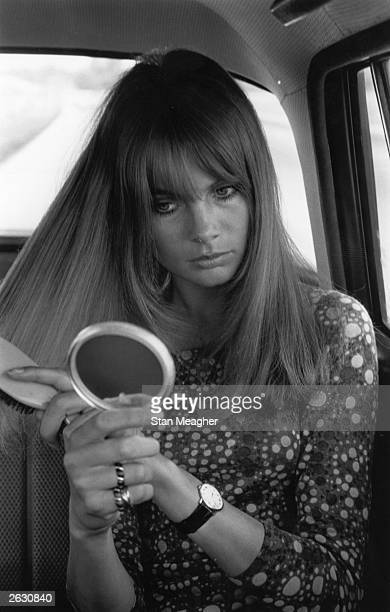 1960's fashion model Jean Shrimpton brushing her hair in the back of a car