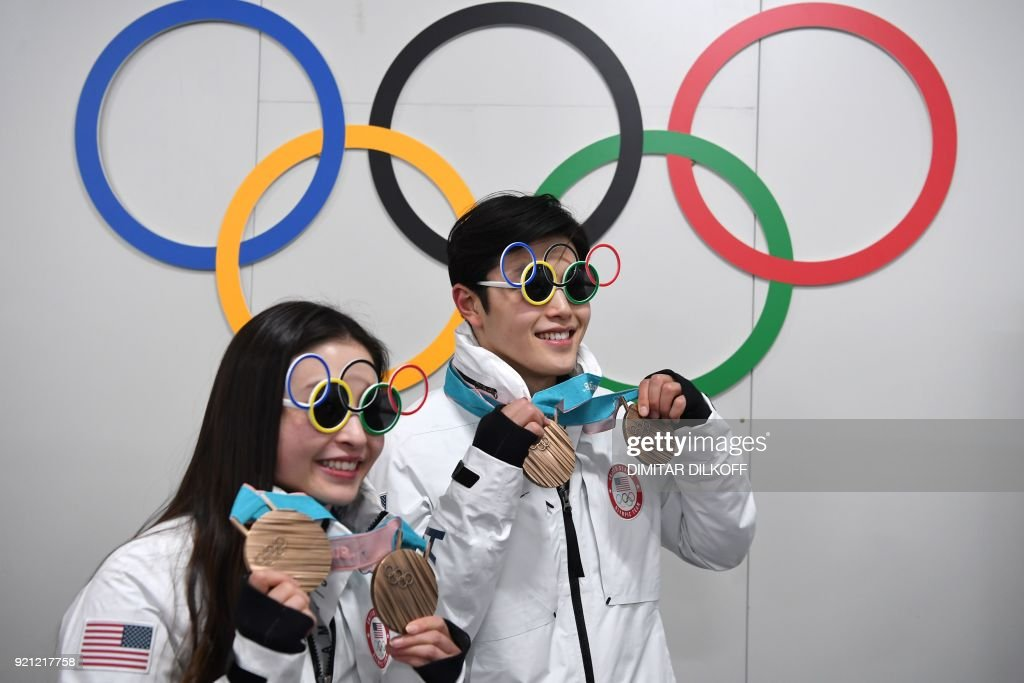 USA's figure skating bronze medallists Maia Shibutani and Alex Shibutani pose in front of Olympic rings backstage at the Athletes' Lounge during the medal ceremonies at the Pyeongchang Medals Plaza during the Pyeongchang 2018 Winter Olympic Games in Pyeongchang on February 20, 2018. / AFP PHOTO / Dimitar DILKOFF