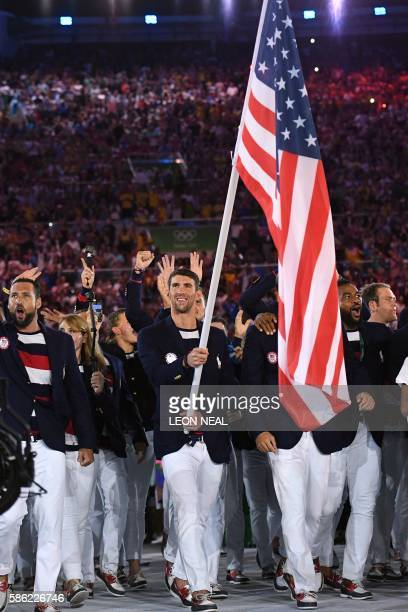 TOPSHOT USA's flag bearer Michael Phelps leads the delegation during the opening ceremony of the Rio 2016 Olympic Games at the Maracana stadium in...