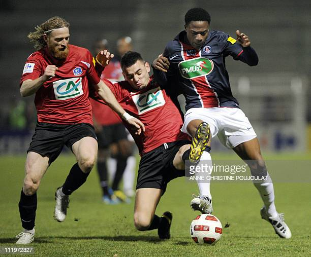 PSG's forward Peguy Luyindula vies with Martigues' forward Mathieu Bouchu and defender Florent Gache during the French Cup football match Martigues...