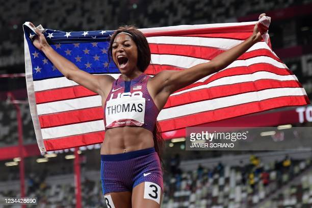 S Gabrielle Thomas celebrates with the flag of the USA after placing third of the women's 200m final during the Tokyo 2020 Olympic Games at the...