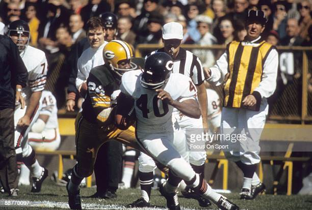 BAY WI CIRCA 1960's Gale Sayers of the Chicago Bears carrying the ball trying to avoid the tackle of Willie Wood of the Green Bay Packers in a late...