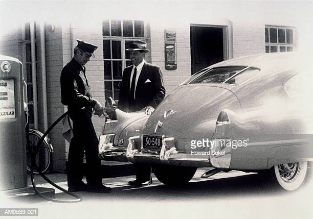 1950's gas station, attendant filling up car, owner watching