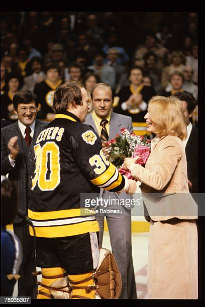 Gerry Cheevers of the Boston Bruins presents Mrs. Orr with flowers at pre game presentation .