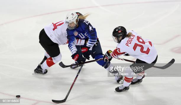 USA's Gigi Marvin is tackled by Canada's MariePhilip poulin and Renata Fast during the Women's Ice Hockey Final at the Gangneung Hockey Centre on day...