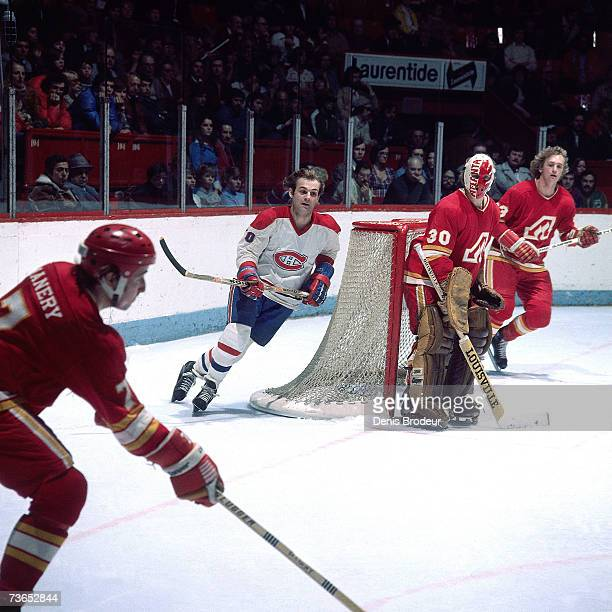 MONTREAL 1970's Goaltender Dan Bouchard of the Atlanta Flames and Guy Lafleur of the Montreal Canadiens look on as Randy Manery plays the puck