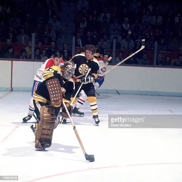 Goaltender Gerry Cheevers of the Boston Bruins attempts to clears the puck against the Montreal Canadiens.