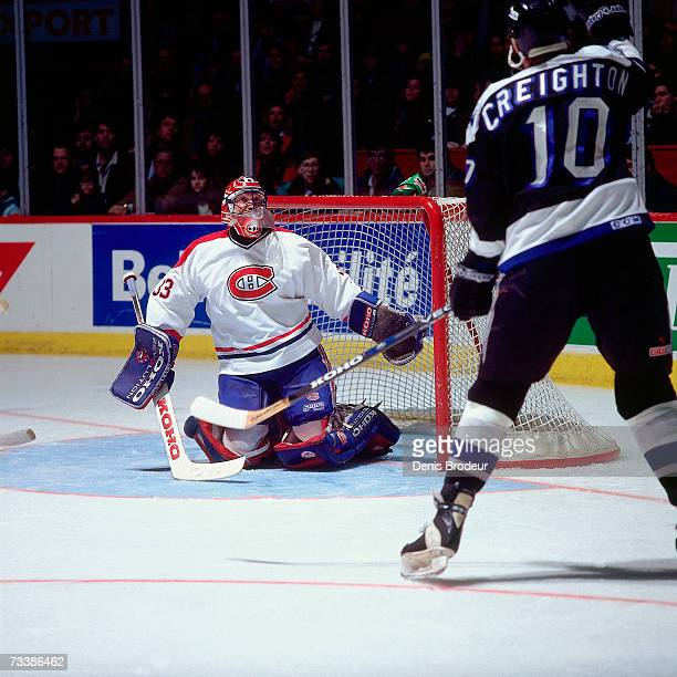 MONTREAL 1990's Goaltender Patrick Roy of the Montreal Canadiens keeps his eyes on the puck against Adam Creighton of the Tampa Bay Lightning during...