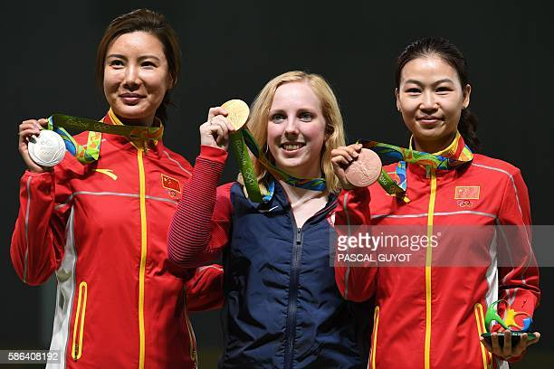 TOPSHOT USA's gold medallist Virginia Thrasher poses on the podium with China's silver medal winner Du Li and China's bronze medallist Yi Siling...
