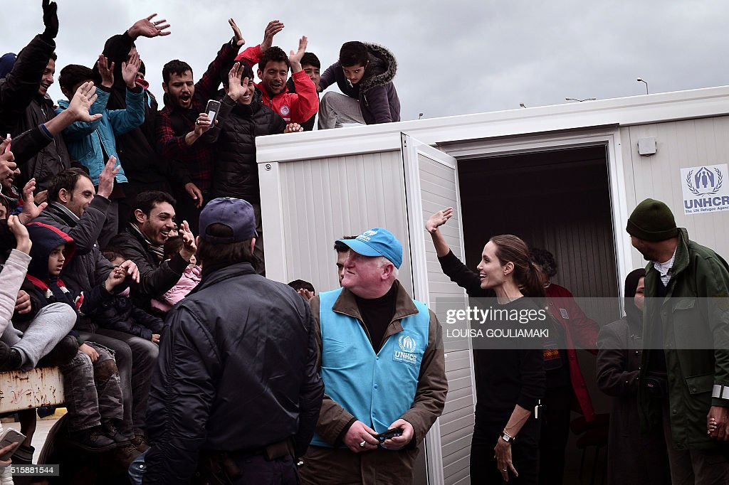 UNHCR's Goodwill Ambassador Angelina Jolie greets (C) refugees and migrants during her visit in the port of Piraeus on March 16, 2016. Some 4000 refugees and migrants are stranded in the port due to Balkans route closure. European leaders scrambled Wednesday to salvage an under-fire deal with Turkey to ease the migrant crisis with a round of shuttle diplomacy on the eve of a crunch summit. / AFP / LOUISA