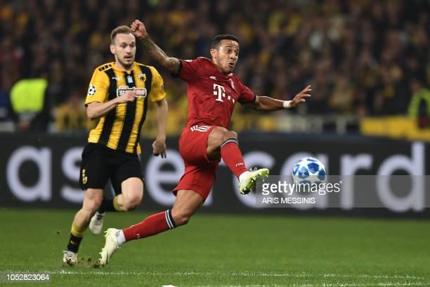 AEK's Greek defender Michalis Bakakis vies with Bayern Munich's Spanish midfielder Thiago Alcantara during the UEFA Champions League football match...