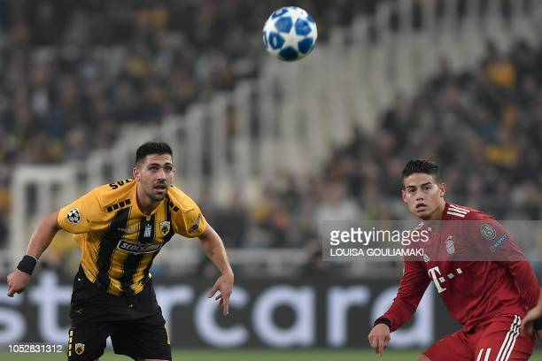 AEK's Greek forward Tasos Bakasetas and Bayern Munich's Colombian midfielder James Rodriguez eye the ball during the UEFA Champions League football...