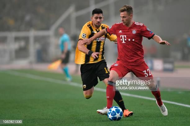 AEK's Greek forward Tasos Bakasetas vies with Bayern Munich's German midfielder Joshua Kimmich during the UEFA Champions League football match...