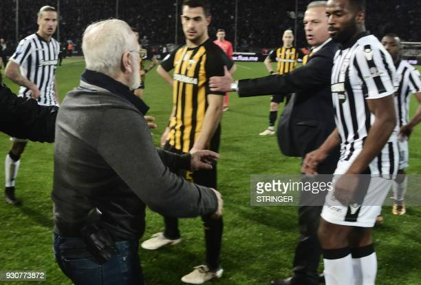 TOPSHOT PAOK's GreekRussian president Ivan Savvidis takes to the pitch carrying a handgun in his waistband after the referee refused a last minute...