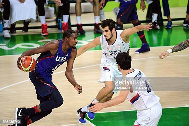 USA's guard Kevin Durant dribbles past Serbia's forward Nikola Kalinic and Serbia's guard Milos Teodosic during a Men's Gold medal basketball match...