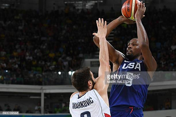 S guard Kevin Durant shoots past Serbia's point guard Stefan Markovic during a Men's Gold medal basketball match between Serbia and USA at the...