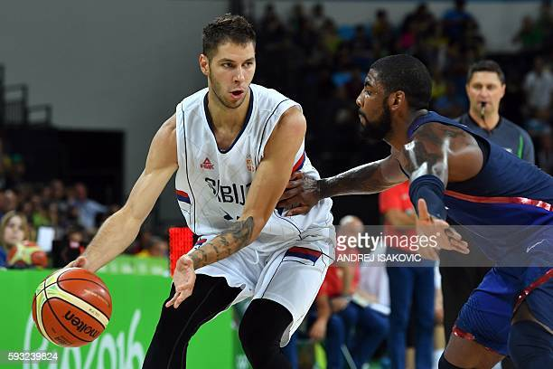 USA's guard Kyrie Irving holds off Serbia's guard Stefan Jovic during a Men's Gold medal basketball match between Serbia and USA at the Carioca Arena...