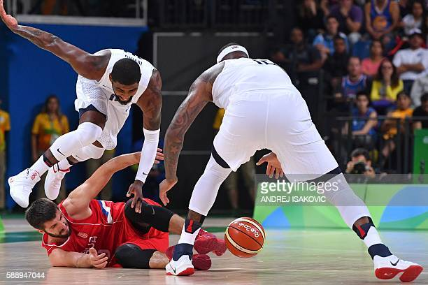 TOPSHOT USA's guard Kyrie Irving jumps over Serbia's point guard Stefan Markovic as USA's centre DeMarcus Cousins grabs the ball during a Men's round...