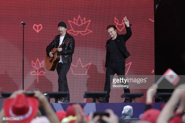 U2's guitarist The Edge left and singer Bono arrive on stage to perform during the Canada Day event on Parliament Hill in Ottawa Ontario Canada on...