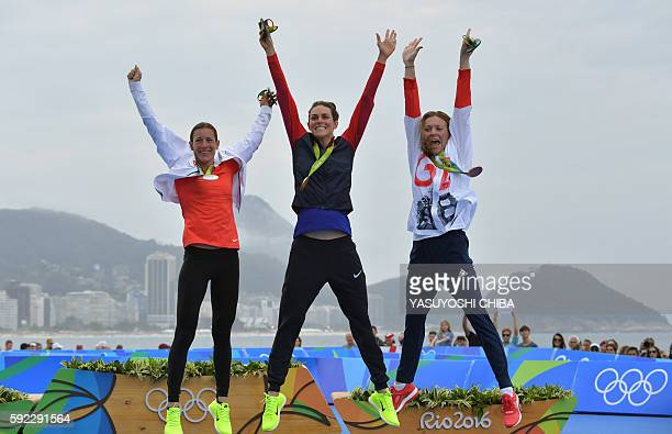 USA's Gwen Jorgensen celebrates with her gold medal next to Switzerland's Nicola Spirig with the silver and Britain's Vicky Holland with bronze on...