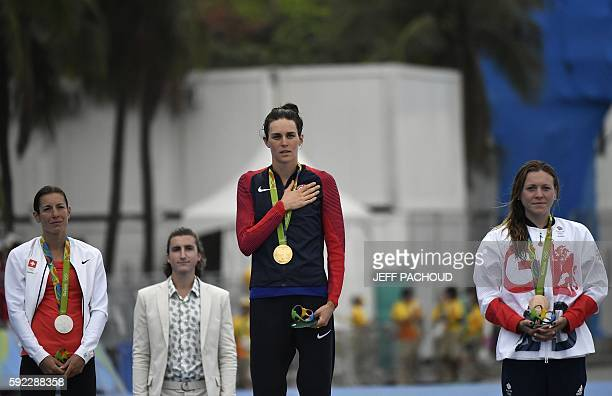 USA's Gwen Jorgensen sings her national anthem after getting the gold medal next to Switzerland's Nicola Spirig with the silver and Britain's Vicky...