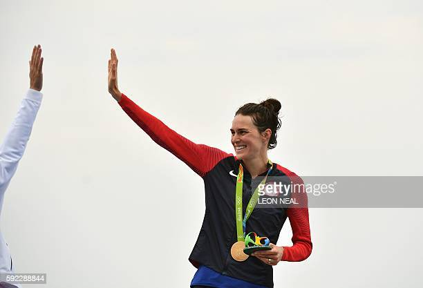 USA's Gwen Jorgensen with her gold medal high fives Switzerland's Nicola Spirig who won the silver on the podium after the women's triathlon at Fort...
