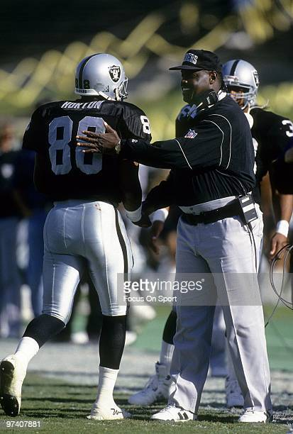 LOS ANGELES CA CIRCA 1990's Head Coach Art Shell of the Los Angeles Raiders give his tight end Ethan Horton coming a pat on the back coming off the...