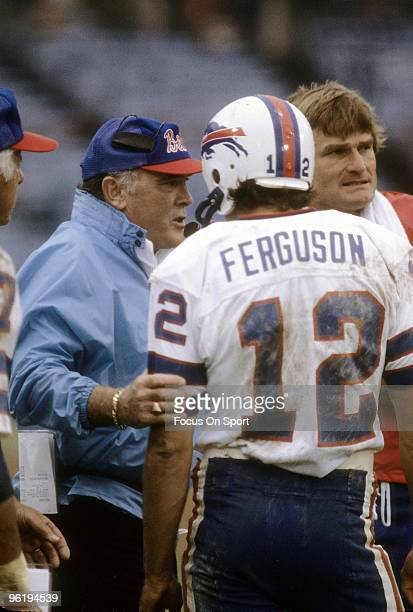 Head Coach Chuck Knox of the Buffalo Bills talks with his quarterback Joe Ferguson on the sidelines during a early circa 1980's NFL football game....