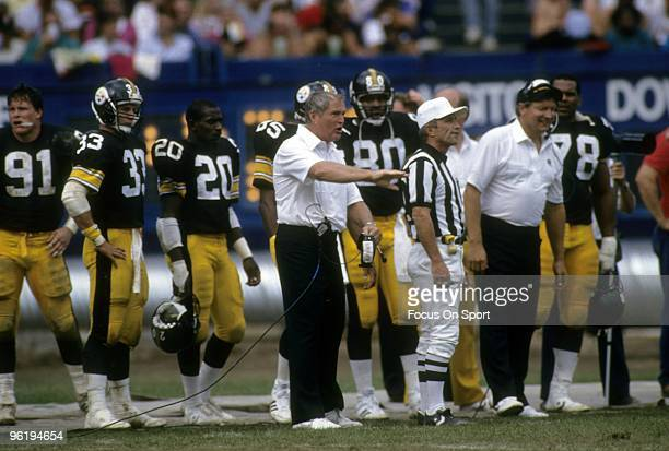 PITTSBURGH PA CIRCA 1980's Head Coach Chuck Noll of the Pittsburgh Steelers coaching his team from the sidelines standing next to an official during...
