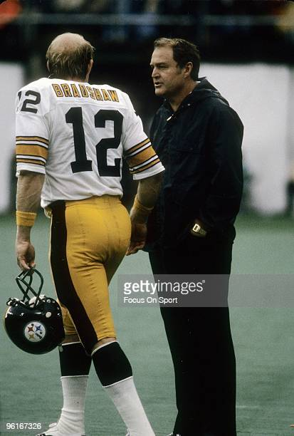 CIRCA 1970's Head Coach Chuck Noll of the Pittsburgh Steelers talks with his quarterback Terry Bracshaw on the sidelines during a late circa 1970's...