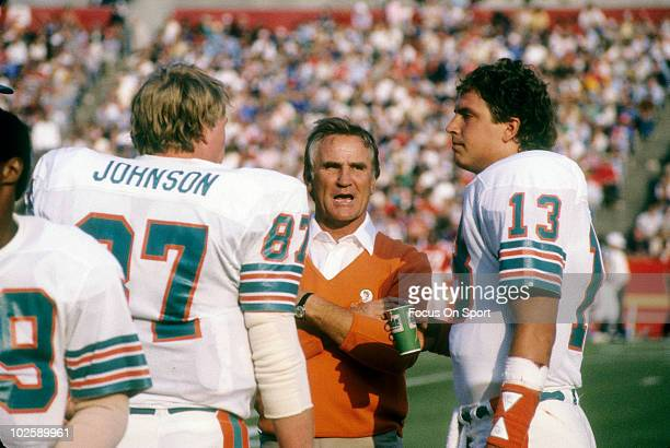 CIRCA 1980's Head Coach Don Shula of the Miami Dolphins in this portrait on the sidelines talking with tight end Dan Johnson and quarterback Dan...