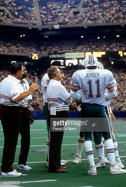 CIRCA 1990's Head Coach Don Shula of the Miami Dolphins in this portrait on the sidelines talking with quarterback Dan Marino and quarterback/wide...