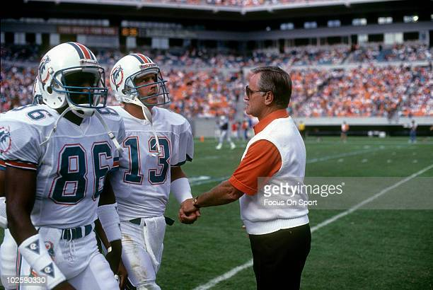 CIRCA 1990's Head Coach Don Shula of the Miami Dolphins in this portrait on the sidelines greats quarterback Dan Marino and wide receiver Fred Banks...