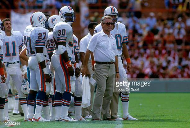 CIRCA 1980's Head Coach Don Shula of the Miami Dolphins in this portrait watching the action from the sidelines standing next to quarterback Don...