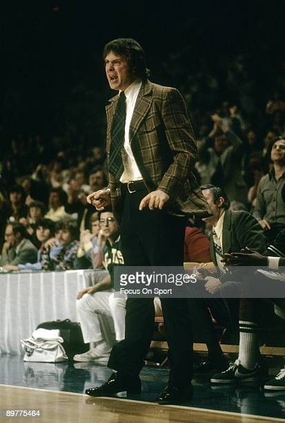 S: Head coach Tom Heinsohn of the Boston Celtics standing, coaching from the bench against the Milwaukee Bucks during a mid circa 1970's NBA...