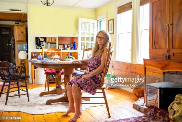 50's hippie woman sitting at country kitchen table in maine during the summer, looking at camera. - catherine ledner stock pictures, royalty-free photos & images