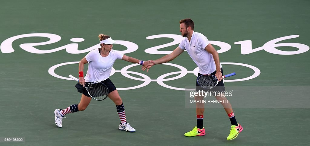 USA's Jack Sock and USA's Bethanie Mattek-Sands react as they play against USA's Venus Williams and USA's Rajeev Ram during their mixed doubles gold medal tennis match at the Olympic Tennis Centre of the Rio 2016 Olympic Games in Rio de Janeiro on August 14, 2016. / AFP / Martin BERNETTI