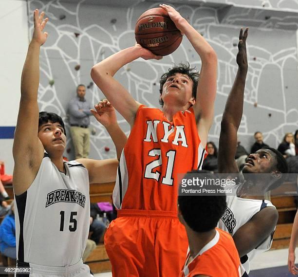 NYA's Jake Malcom shoots the ball between PTA's Jon Krebs and JP Tshamala as Pine Tree Academy boys basketball host North Yarmouth Academy