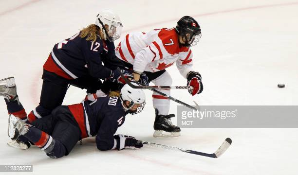 USA's Jenny Potter and Angela Ruggiero battle with Canada's Cherie Piper for control of the puck in the Women's Gold Medal Hockey game during the...