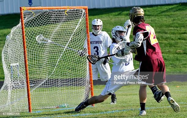 TA's Jon Camire scores against Westbrook's goal keeper Alex Leblanc as Westbrook HS boys lacrosse hosts Thornton Academy