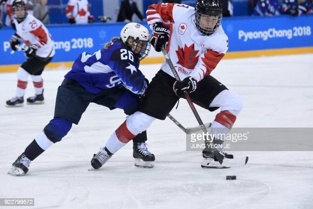 USA's Kendall Coyne fights for the puck with Canada's Jocelyne Larocque in the women's gold medal ice hockey match between the US and Canada during...