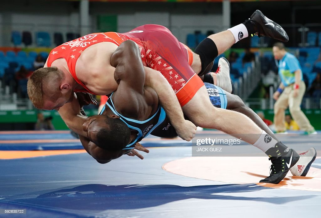 TOPSHOT - USA's Kyle Frederick Snyder (red) wrestles with Cuba's Javier Cortina Lacerra in their men's 97kg freestyle round of 16 match on August 21, 2016, during the wrestling event of the Rio 2016 Olympic Games at the Carioca Arena 2 in Rio de Janeiro. / AFP / Jack GUEZ