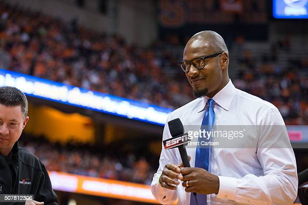 ESPN's LaPhonso Ellis performs a courtside analysis while wearing 'dress like Jim Boeheim glasses during the game between the Syracuse Orange and the...