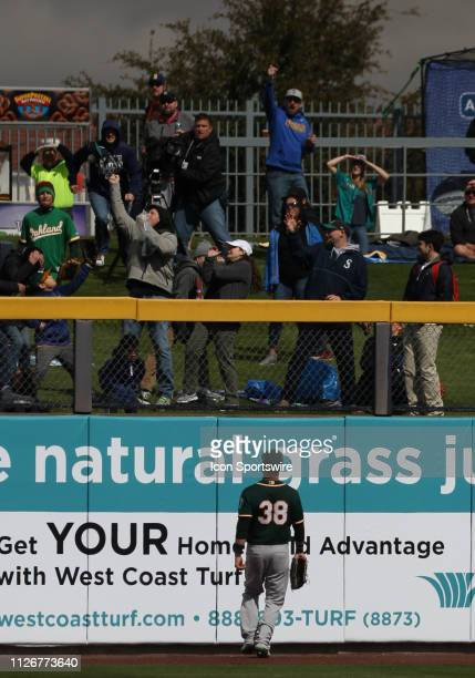 A's Left fielder Nick Martini watches Mariners' Mitch Haniger's home run leave the field and get caught by a fan in a Cactus League Spring training...