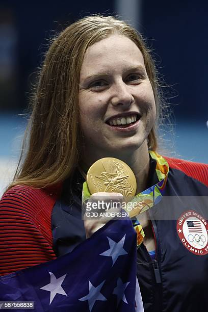 USA's Lilly King wrapped in her national flag poses with her gold medal on the podium after she won the Women's 100m Breaststroke Final during the...