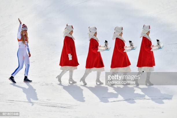 TOPSHOT USA's Lindsey Vonn third placed follows hostesses for the victory ceremony of the women's Downhill at the Jeongseon Alpine Center during the...